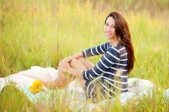 Mädchen, das auf einer Steppdecke auf einem Gebiet mit Sonnenblumen sitzt Stockbilder