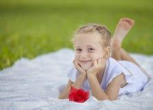 Mädchen, das mit roter Blume lächelt stockbilder