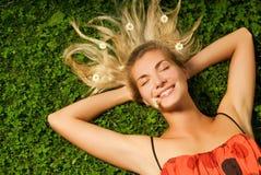 Mädchen, das auf einer Wiese sich entspannt Lizenzfreie Stockfotografie