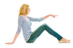 Mädchen, das auf Fußboden sitzt und auf Exemplarplatz zeigt Stockbild