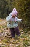 Mädchen, das auf gelben Blättern läuft stockfotos