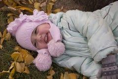 Mädchen, das auf gelben Blättern lacht stockbilder