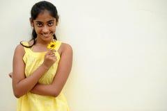 Mädchen, das auf gelber Wand mit Blume aufwirft Lizenzfreie Stockbilder