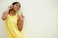Mädchen, das auf gelber Wand mit Blume aufwirft Lizenzfreie Stockfotografie