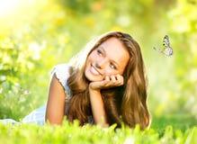 Mädchen, das auf grünem Gras liegt Stockbild