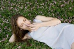 Mädchen, das auf grünem Gras mit Blumen liegt Lizenzfreies Stockfoto