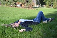 Mädchen, das auf Gras liegt Stockbilder