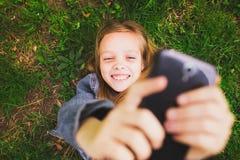 Mädchen, das auf Gras mit Handy legt Stockbilder