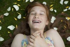 Mädchen, das auf Gras und Blumenblätter legt Lizenzfreie Stockfotografie