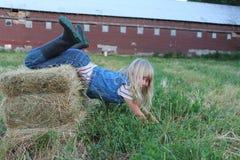 Mädchen, das auf Heu-Ballen sich neigt Stockfotografie