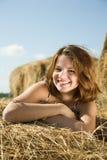 Mädchen, das auf Heu genießt Lizenzfreie Stockfotografie