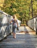 Mädchen, das auf Holzbrücke geht Lizenzfreie Stockfotos