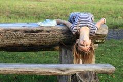 Mädchen, das auf Holztisch liegt Stockfoto
