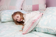 Mädchen, das auf ihrem Bett spielt Stockbilder