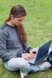 Mädchen, das auf ihrem Laptop beim Betrachten des Störungsbesuchs schreibt Stockfotografie