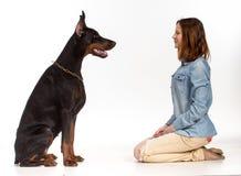 Mädchen, das auf ihren Knien vor einem großen schwarzen Hund sitzt Lizenzfreie Stockfotografie