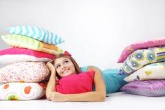 Mädchen, das auf Kissen stillsteht Stockfoto