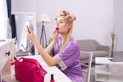 Mädchen, das auf Lippenstift sich setzt Lizenzfreie Stockfotos