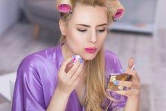 Mädchen, das auf Lippenstift sich setzt Stockfotografie