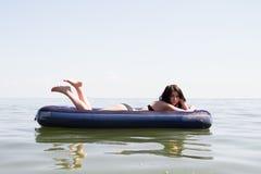 Mädchen, das auf Luftmatraze im Meer ein Sonnenbad nimmt Stockbild