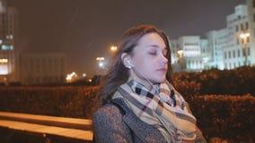 Mädchen, das auf Musik auf Kopfhörern und Betrieb durch die Abendlichter der Stadt unter den Häusern hört kalt snowing stock video