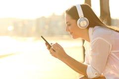 Mädchen, das auf Musikdownloadinglied unter Verwendung des Telefons hört lizenzfreie stockbilder