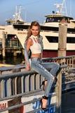 Mädchen, das auf Pier mit Schiff auf dem Hintergrund aufwirft Stockbilder
