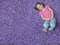 Mädchen, das auf purpurroten Blumen liegt Stockfoto