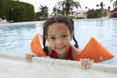 Mädchen, das auf Rand des Swimmingpools sich entspannt Stockfotos