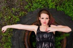 Mädchen, das auf Reifen legt Stockfotos