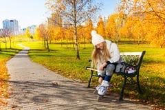 Mädchen, das auf Rollschuhe sich setzt Lizenzfreie Stockfotografie