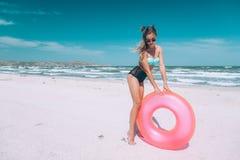 Mädchen, das auf rosa lilo auf dem Strand sich entspannt lizenzfreie stockfotografie