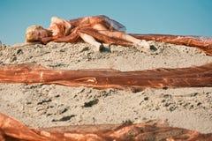 Mädchen, das auf Sand im orange Tuch liegt Stockbilder
