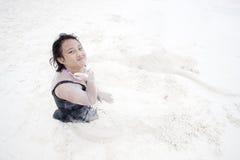 Mädchen, das auf Sandstrand spielt Stockbild