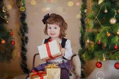 Mädchen, das auf Schlitten sitzt und Geschenkbox unter Weihnachtsbaum hält stockbild