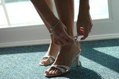 Mädchen, das auf Schuhe sich setzt. Stockfoto