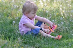 Mädchen, das auf Schuhe sich setzt Stockbild
