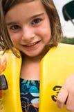 Mädchen, das auf Schwimmweste sich setzt Stockfotografie
