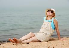 Mädchen, das auf Seestrand sich entspannt Lizenzfreies Stockfoto