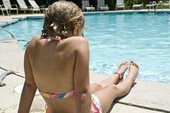 Mädchen, das auf Seite des Pools sitzt Stockbilder