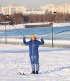 Mädchen, das auf Skis mit Skipolen steht Stockfotos
