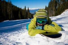 Mädchen, das auf Snowboard liegt Lizenzfreie Stockbilder