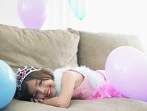Mädchen, das auf Sofa With Balloons liegt Stockfotos