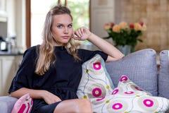 Mädchen, das auf Sofa in einem Aufenthaltsraum sitzt stockbild