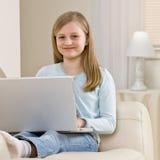 Mädchen, das auf Sofa im Wohnzimmer sich entspannt Stockfoto