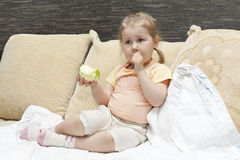 Mädchen, das auf Sofa mit Apfel sitzt Stockbilder