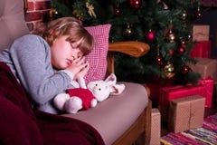 Mädchen, das auf Sofa nahe Weihnachtsbaum mit Geschenken schläft Lizenzfreies Stockfoto