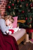 Mädchen, das auf Sofa nahe Weihnachtsbaum mit Geschenken schläft Stockfotografie
