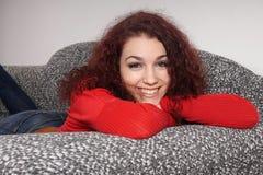 Mädchen, das auf Sofa sich entspannt Stockbilder