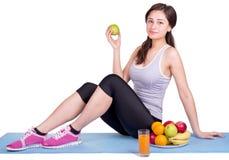 Mädchen, das auf Sportmatte nahe bei Frucht sitzt Lizenzfreies Stockfoto